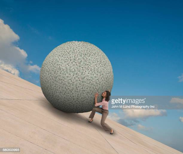 Mixed race businesswoman pushing boulder on slope