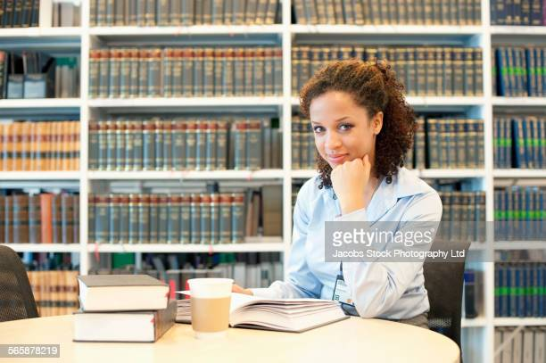 mixed race businesswoman reading at desk in law library - lawyer stock pictures, royalty-free photos & images