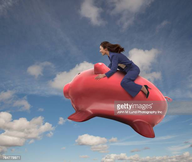 mixed race businesswoman riding flying piggy bank in sky - john lund stock pictures, royalty-free photos & images