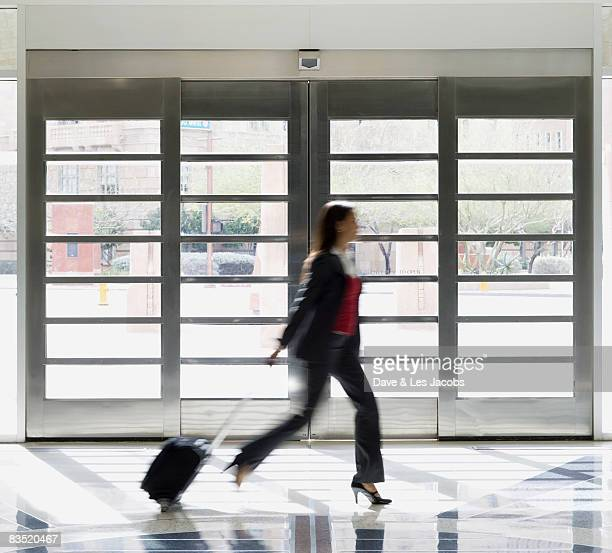 Mixed race businesswoman rushing with suitcase