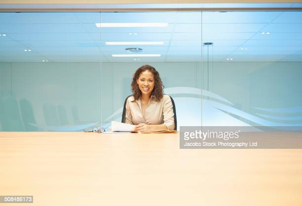 Mixed race businesswoman sitting at conference table