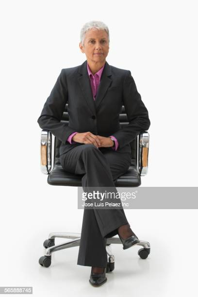 Mixed race businesswoman sitting in office chair