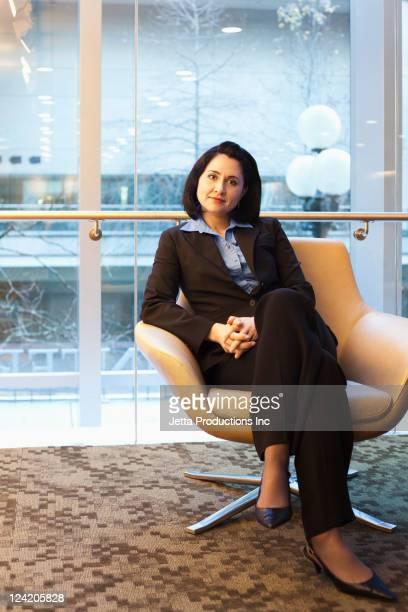 Gemischtes Geschäftsfrau sitzt im Büro
