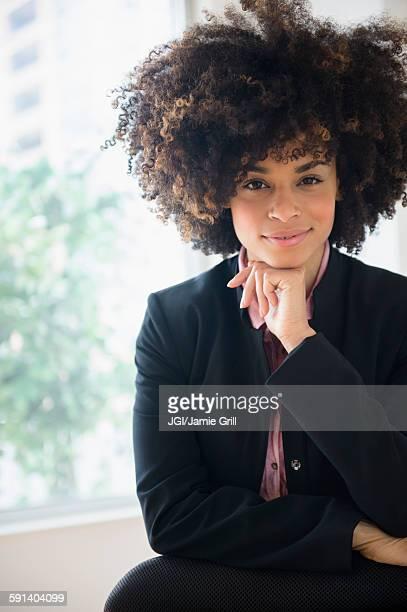 mixed race businesswoman sitting near window - tenue soignée photos et images de collection