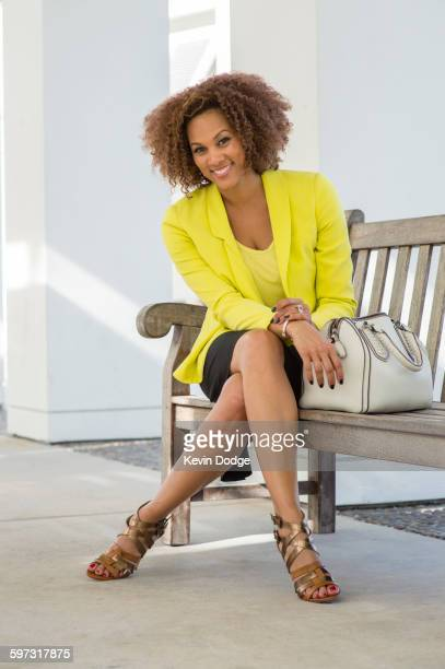 Mixed race businesswoman sitting on bench