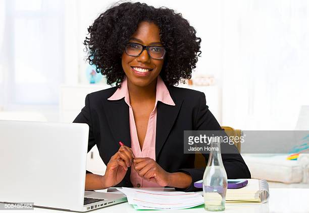 Mixed race businesswoman smiling at desk