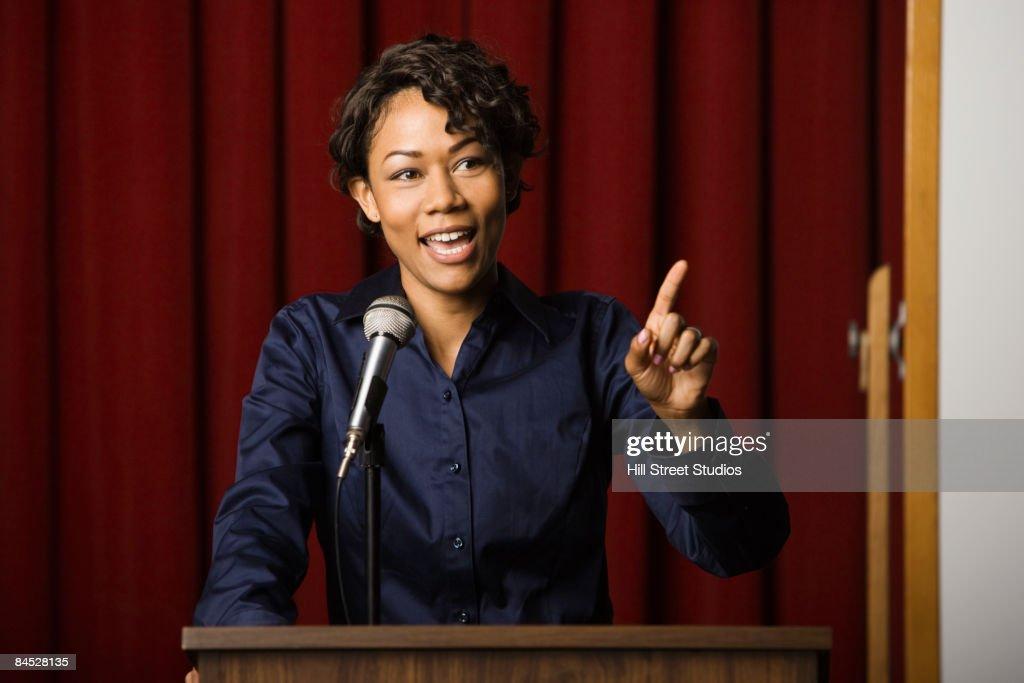 Mixed race businesswoman speaking at podium : Foto de stock