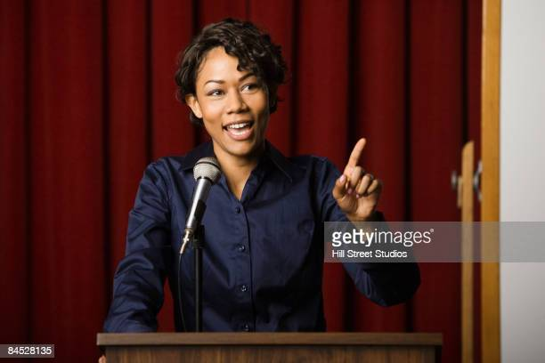 mixed race businesswoman speaking at podium - debate stock photos and pictures