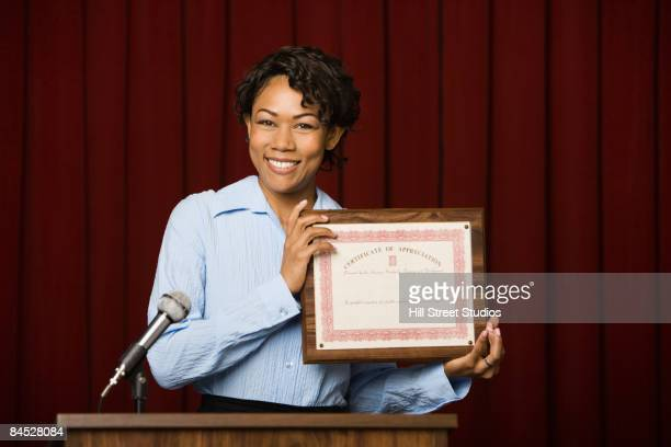 mixed race businesswoman speaking at podium with certificate - preisverleihung stock-fotos und bilder