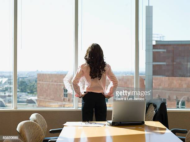 mixed race businesswoman standing in conference room - one mid adult woman only stock pictures, royalty-free photos & images