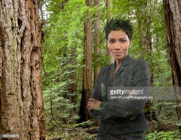 Mixed race businesswoman standing in forest