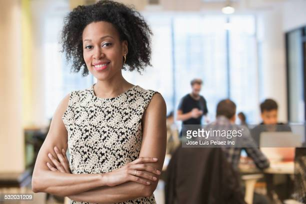 Mixed race businesswoman standing in office