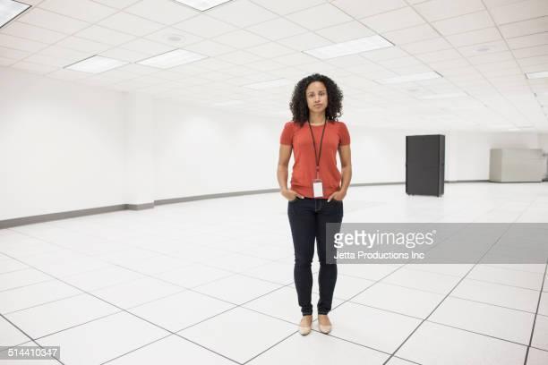Mixed race businesswoman standing in server room