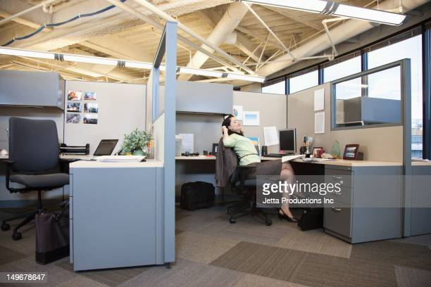 mixed race businesswoman stretching at desk in cubicle - jetta productions stock pictures, royalty-free photos & images