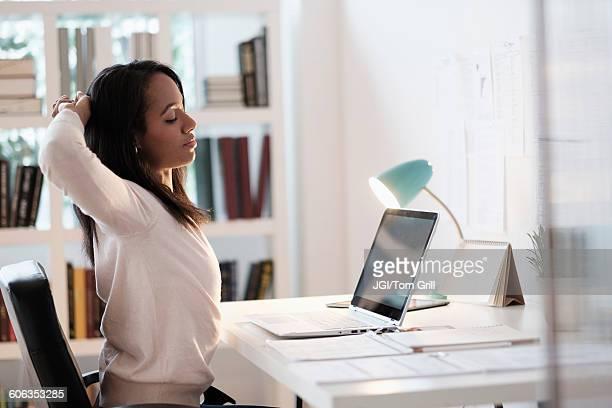 mixed race businesswoman stretching at desk - strekken stockfoto's en -beelden