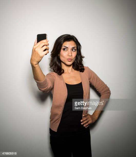Mixed race businesswoman taking cell phone picture