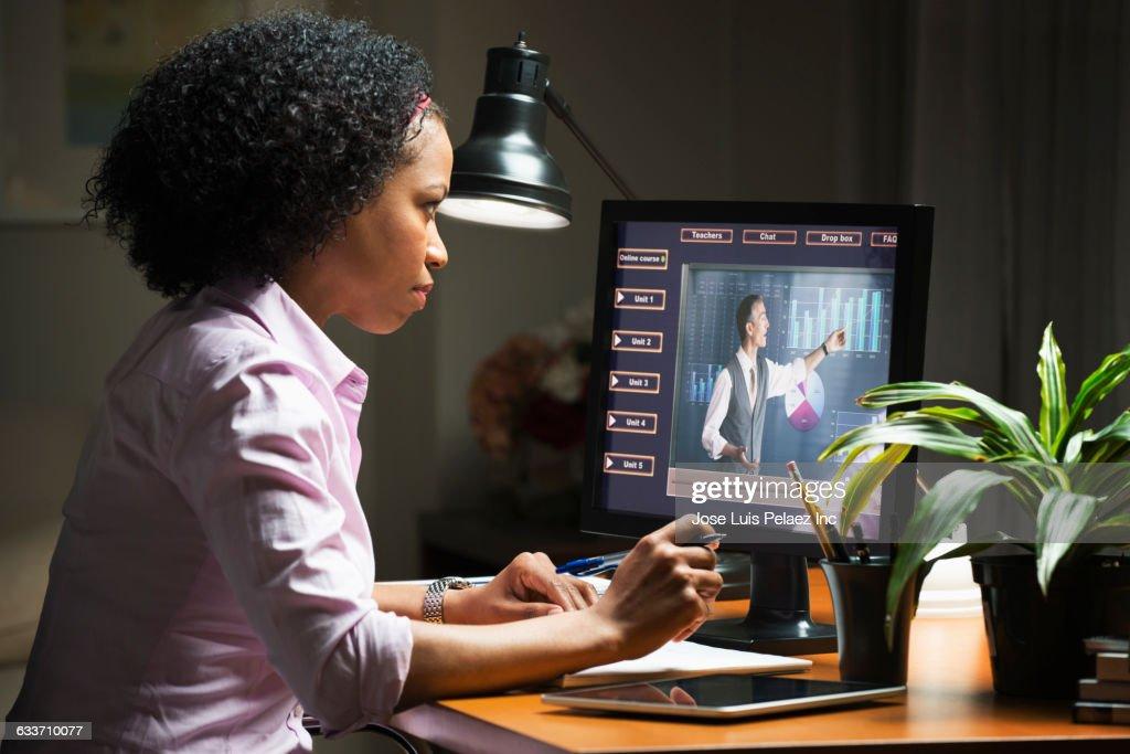 Mixed race businesswoman taking online class on computer : ストックフォト