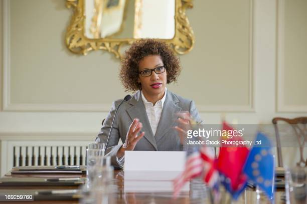 mixed race businesswoman talking in microphone - politician stock pictures, royalty-free photos & images