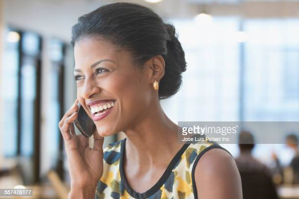 Mixed race businesswoman talking on cell phone in office