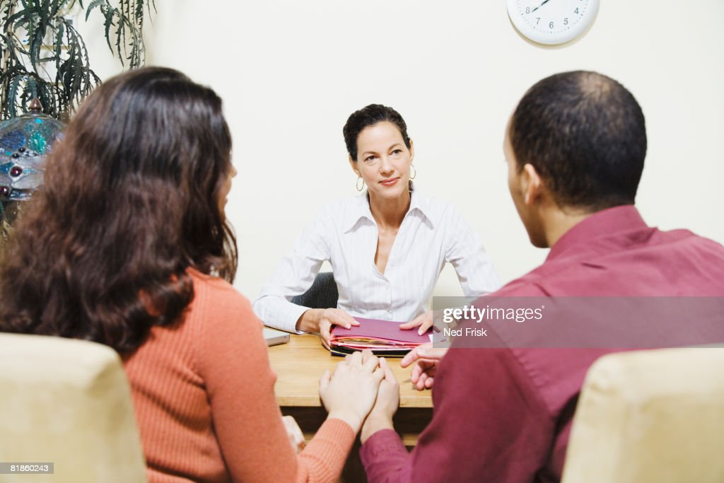 Mixed Race businesswoman talking to clients : Stock Photo