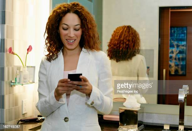 Mixed race businesswoman text messaging on cell phone