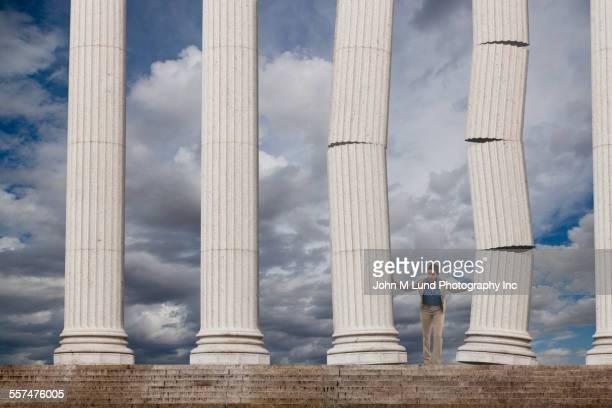 mixed race businesswoman toppling columns - architektonische säule stock-fotos und bilder