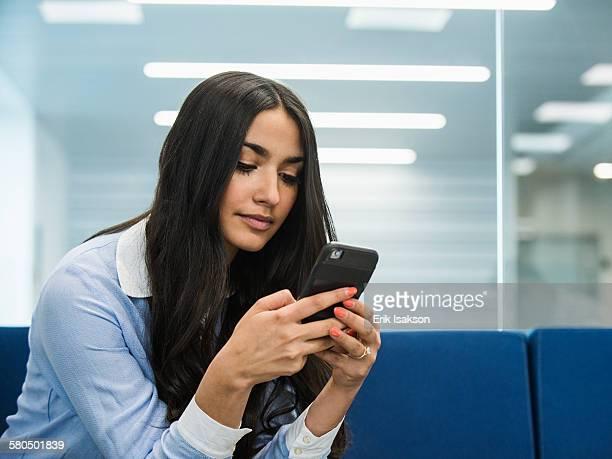 mixed race businesswoman using cell phone in office lobby - cabelo castanho - fotografias e filmes do acervo
