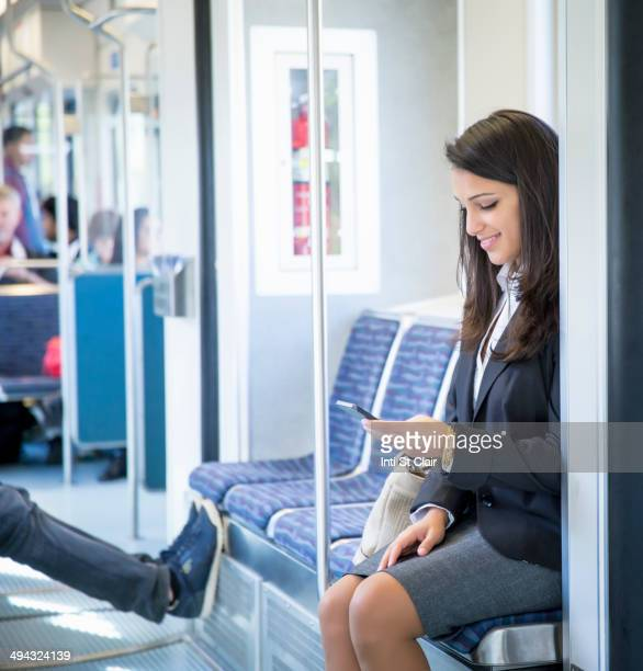 Mixed race businesswoman using cell phone on train