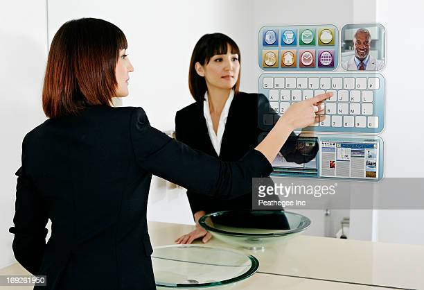 Mixed race businesswoman using computer in mirror
