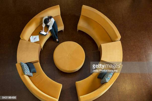 Mixed race businesswoman using digital tablet on circular sofa