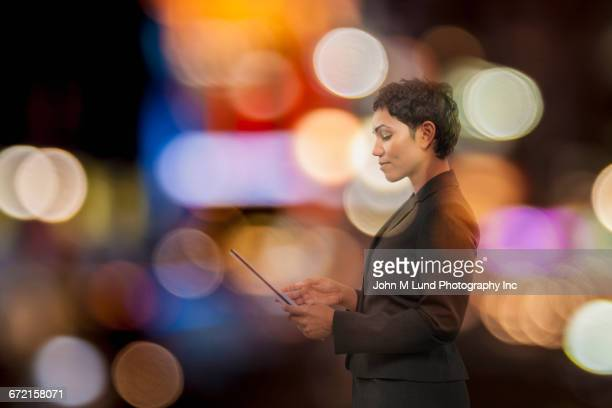 Mixed Race businesswoman using digital tablet with multicolor circles