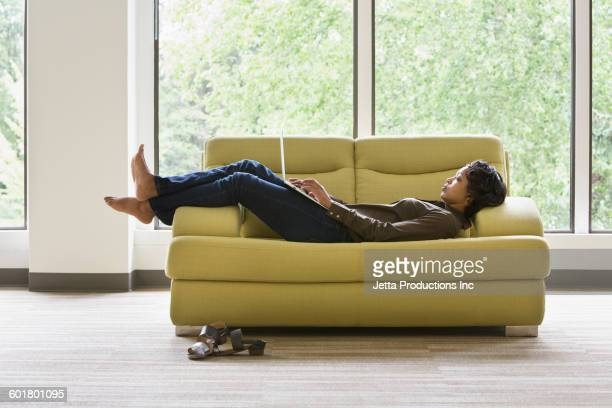 Mixed race businesswoman using laptop on sofa