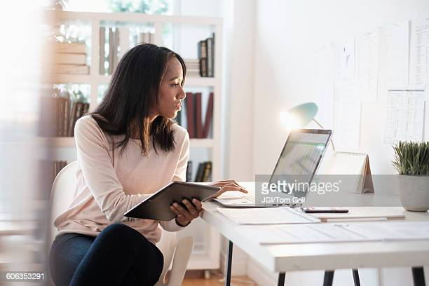 Mixed race businesswoman using laptop