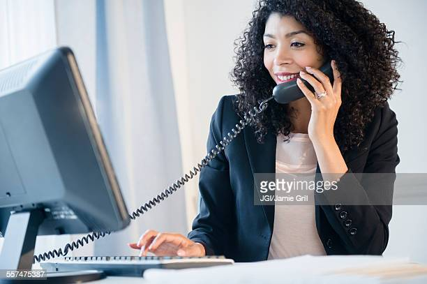 Mixed race businesswoman using telephone and computer in office