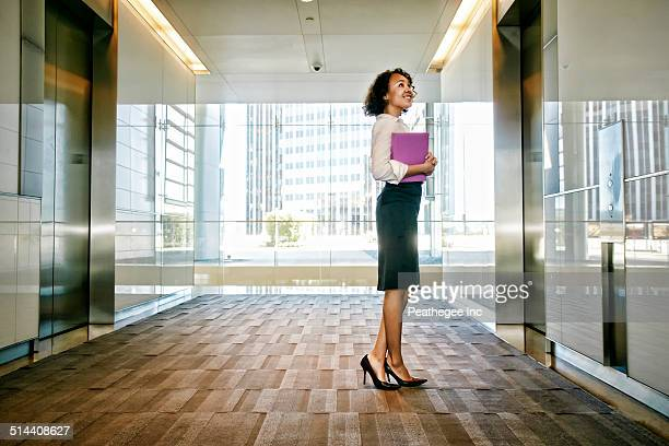Mixed race businesswoman waiting for elevator in lobby