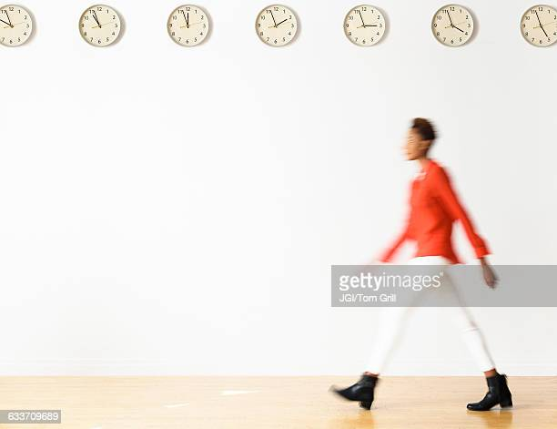mixed race businesswoman walking under clocks - motion blur stock photos and pictures