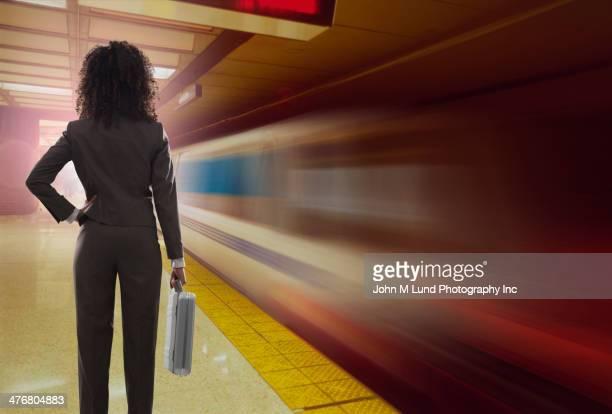 Mixed race businesswoman watching train leave platform