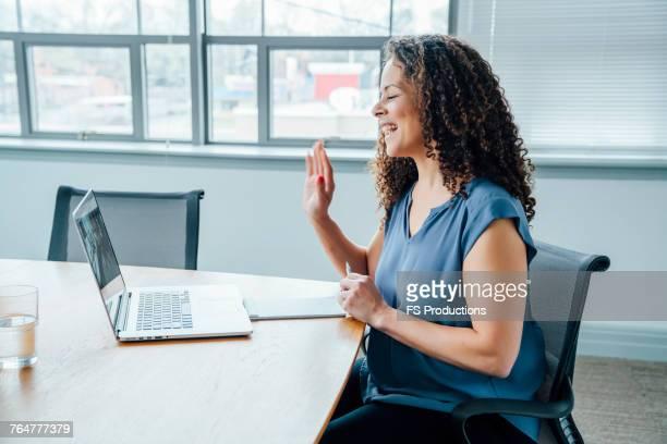 mixed race businesswoman waving on video conference - zwaaien gebaren stockfoto's en -beelden