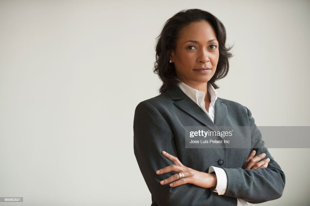 Mixed race businesswoman with arms crossed : Foto stock