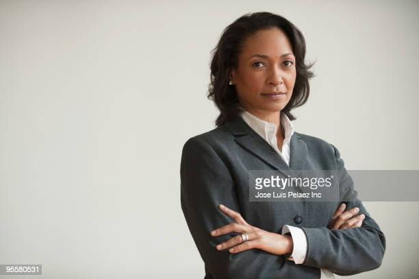 Mixed race businesswoman with arms crossed