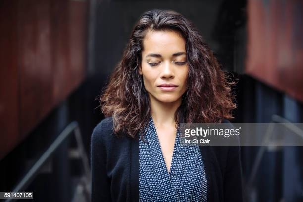 mixed race businesswoman with eyes closed in office - eyes closed stock pictures, royalty-free photos & images