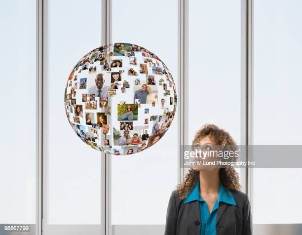Mixed race businesswoman with floating globe of faces