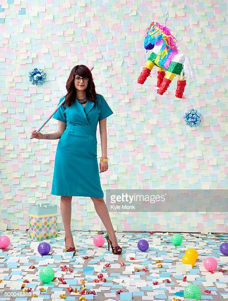 Mixed race businesswoman with pinata in office