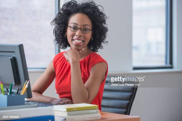 mixed race businesswoman working in office - werkneemster stockfoto's en -beelden