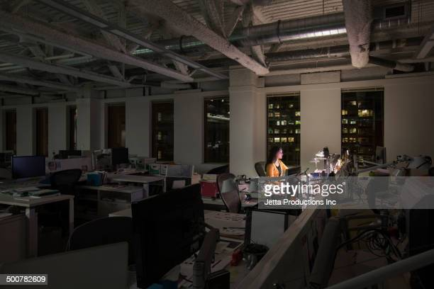 Mixed race businesswoman working late in office