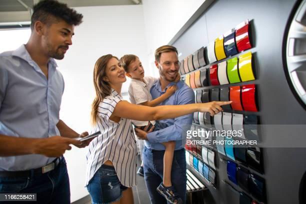 blandad racerbils försäljare som erbjuder hjälp till en familj med ett barn att välja rätt färg för sin nya bil i en bilsalong - partire bildbanksfoton och bilder
