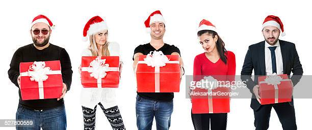mixed race characters smiling with christmas hats holding gift boxes - santa hat stock photos and pictures