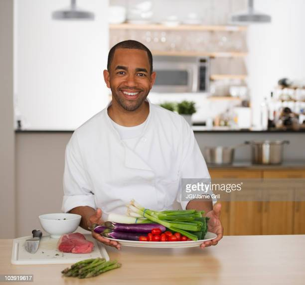 Mixed race chef holding plate of vegetables