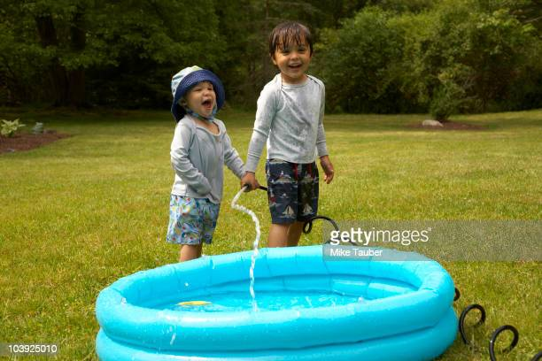 Mixed race children filling inflatable pool
