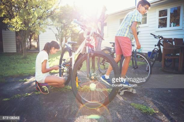 Mixed race children fixing bicycles in backyard